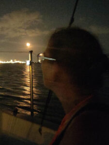 Barb looking at the moon rise while navigating up the Delaware River